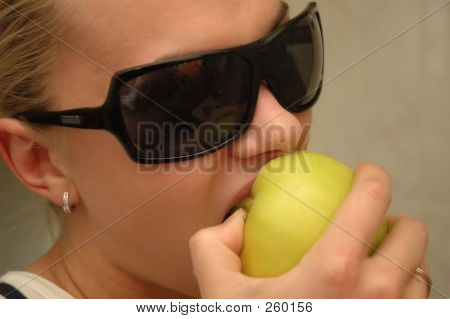 Girl With Sun Glasses Eats Green Apple