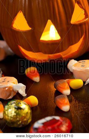 Scatter Halloween candies and orange pumpkin with light