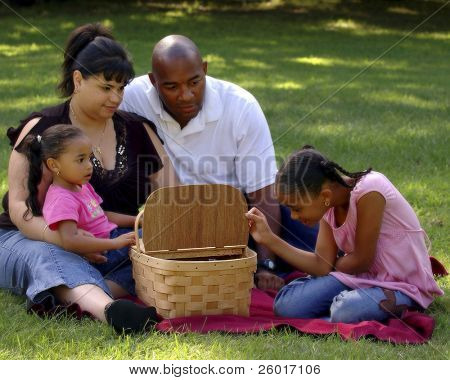 Child peeking into picnic basket with her bi-racial family looking on.