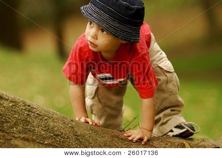 Small boy climbing over fallen tree.