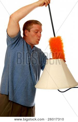 Man whistling while cleaning a lampshade with a fluffy orange duster.  Isolated on white.