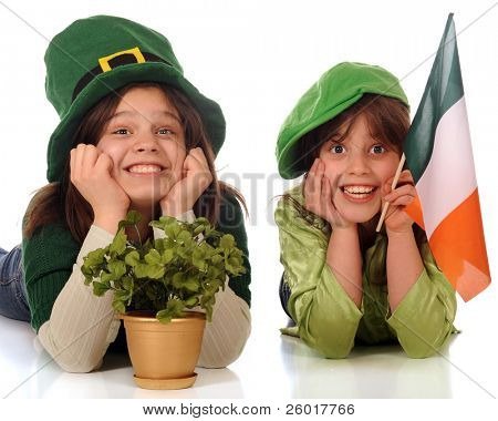 Two happy sisters celebrating St. Patrick's Day wearing green and over-sized hats, and with a gold pot of shamrocks and Irish flag.  Isolated on white.