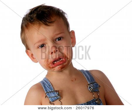Close-up of an adorable toddler boy in tears after eating a fudgecycle, the messy evidence surrounding his mouth.  Isolated on white.