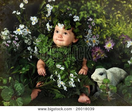A happy baby girl clothed in leaves surrounded by foliage and a cute gray bunny.