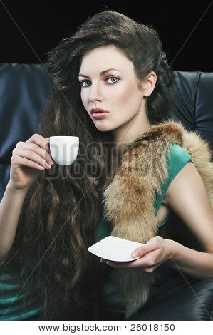 Young Elegant Girl In Green With Cup, She Is Bringigng The Cup To Her Lips