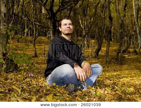 Young handsome man laying in autumn forest