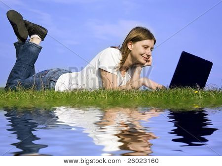Young blonde girl working on laptop outdoors