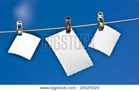 Blank photographs hanging on a clothesline against a blue sky