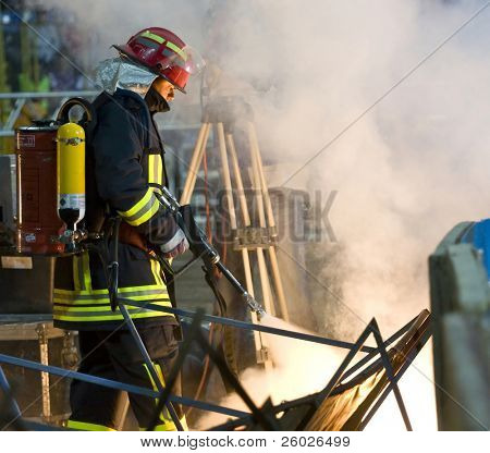 TARGU-JIU, ROMANIA - JUNE 13: Fireman with extinguisher fighting a fire during the Romanian Cup Final soccer game, June 13, 2009 in Targu-Jiu, Romania