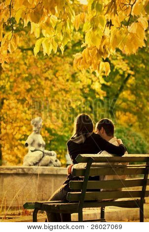 Romantic couple on a bench in the autumn park