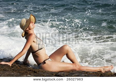woman with hat sunbathing on rocks near big waves