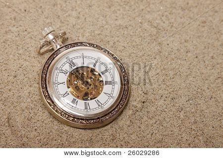 Old pocket watch buried in sand. Lost time concept.