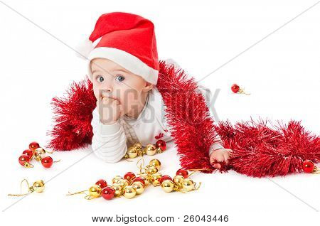 Niño ataviado con un sombrero de Santa y jugando con adornos. Aislado sobre fondo blanco