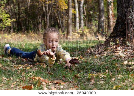 Eine lächelnde Mädchen ist auf Gras in der Gesamtstruktur zur Festlegung von