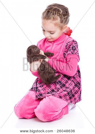 a smiling girl is playing with a kitten. isolated on a white background