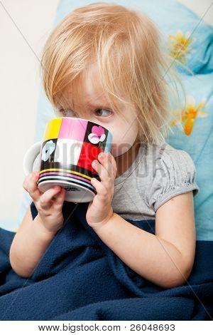 Little sick girl is drinking tea