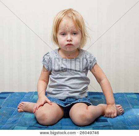 a little sick girl is sitting near the bed