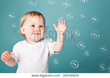 A little funny boy is playing with bubbles on a blue background