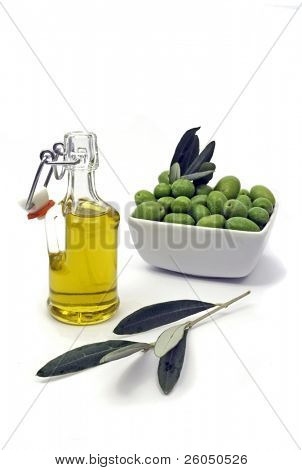 Bottle of extra virgin olive oil with fresh green olives