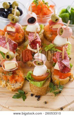 Bruschetta, italian cold buffet with tomato, olive, ham and herbs