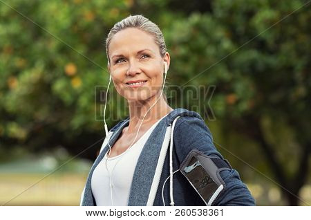 poster of Portrait of a smiling healthy woman with earphones standing in park after running. Proud mature woma