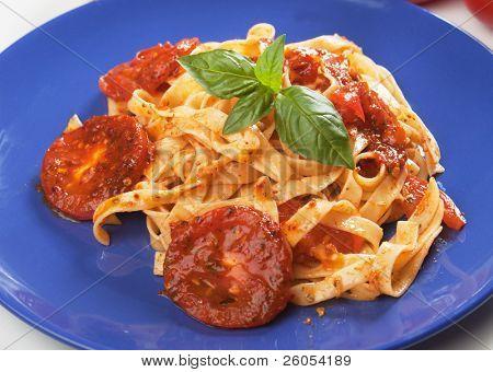 Italian milanese pasta with tomato sauce and fresh basil