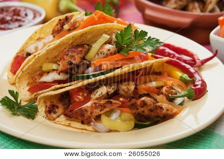 Grilled chicken meat, vegetable and hot chili peppers in taco shells