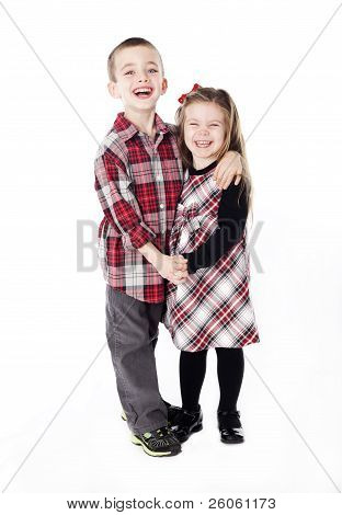 Siblings Embracing In Holiday Clothes