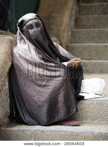 Black eyes - Woman sitting on steps in full hijab (wearing paranja)