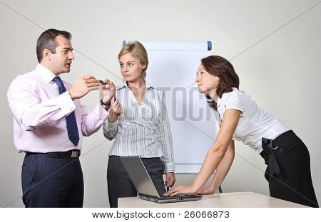 Three office workers, a man giving a presentation on a flip chart trying to convince the others
