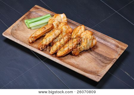 Grilled chicken wings served on wooden board