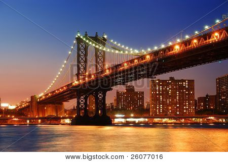 New York City Manhattan Bridge over Hudson River with skyline after sunset night view illuminated with lights viewed from Brooklyn.