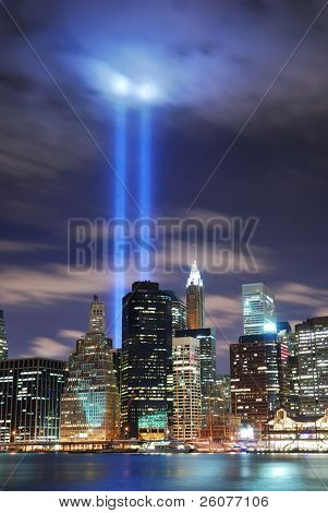 Remember September 11. New York City Manhattan panorama view at night with office building skyscrapers skyline illuminated over Hudson River and two light beam in memory of September 11.