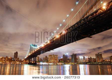 New York City Manhattan Bridge with city skyline at night illuminated over Hudson River.