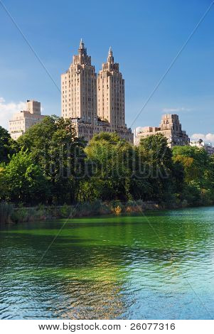 New York City Central Park urban Manhattan skyline with skyscrapers and trees lake reflection with blue sky and white cloud.