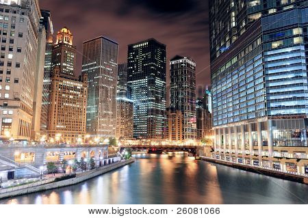 Chicago River Walk with urban skyscrapers illuminated with lights and water reflection at night.