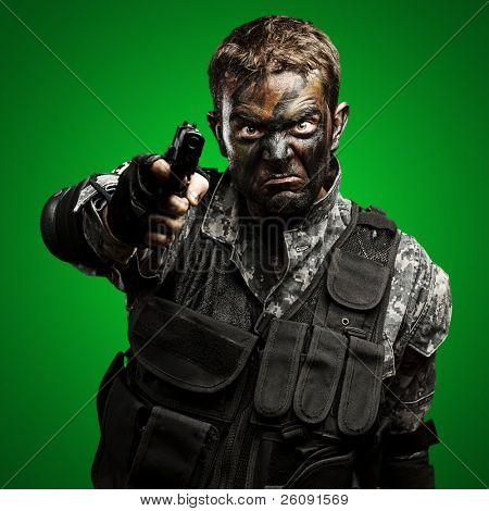 portrait of furious soldier with urban camouflage pointing with gun over green background