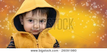 Boy in yellow on yellow snowflake background with space for copy.