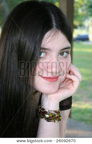 Beautiful Tween Girl Sitting Outside. Focus on girl's left eye and hand.