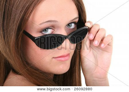 Beautiful Fourteen Year Old Girl Looking Over Sunglasses.  Brown hair and hazel eyes.
