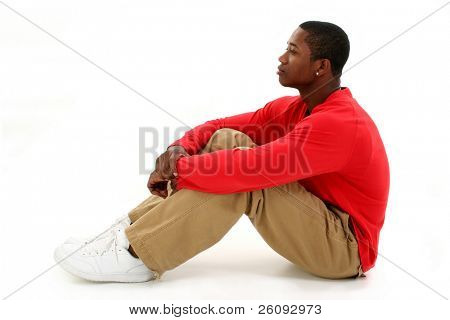 Casual young man in red long sleeve shirt sitting on white backdrop thinking.  Full body shot in studio over white.