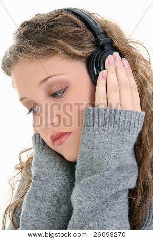 Hermosa chica de dieciséis año de edad adolescente escuchando auriculares. Disparó en estudio sobre el blanco.