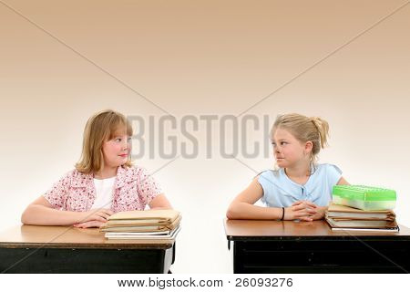 Two pretty little girls looking nervous on the first day back to school.  Shot in studio.  Brown background with space for copy.