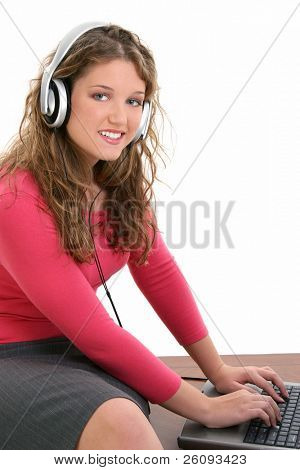 Beautiful Teen girl sitting on desk wearing headphones working on laptop. Shot in studio over white.