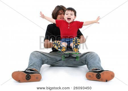 Teen Boy and Toddler Boy Playing Together With Skateboard. Shot in studio over white.