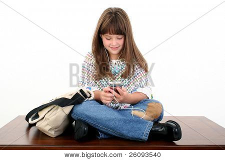 Young girl listening to music, sitting on table next to book bag.  Shot in studio over white.