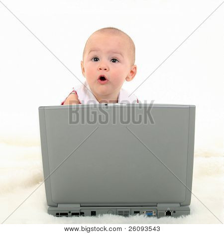 Baby girl with surprised express working on laptop. Shot in studio over white.
