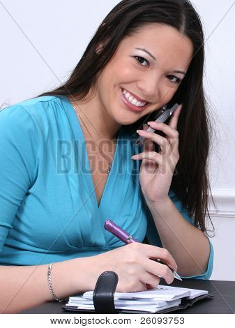 Smiling Asian-American woman with cellphone and datebook.