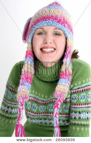 Beautiful teen girl with dazzling smile in green sweater and crazy winter hat.  Shot in studio over white.
