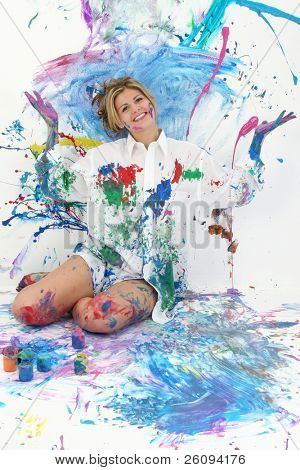 "Beautiful young woman sitting in paint covered studio.  Paint splattered on walls, floor, model.  Shot in studio over ""white"".  :)"